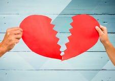 Manos de los pares que llevan a cabo un corazón quebrado Imagen de archivo libre de regalías