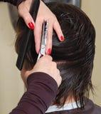 Manos de los peluqueros que cortan el pelo negro Imagen de archivo libre de regalías