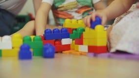 Manos de los pequeños niños que juegan al constructor metrajes