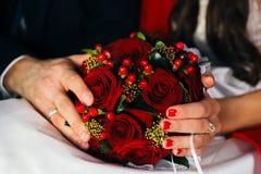 Manos de los recienes casados que sostienen un ramo de la boda Fotografía de archivo libre de regalías