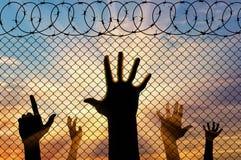Manos de los refugiados de la silueta cerca de la cerca de la frontera Imagenes de archivo
