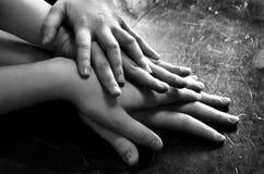 Manos de niños encima de otras manos para el amor y el trabajo en equipo Imagen de archivo libre de regalías