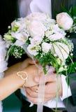 Manos de novia y del novio con el ramo de la boda Fotos de archivo