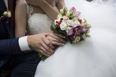 Manos de novia y del novio con los anillos de bodas Imagen de archivo libre de regalías