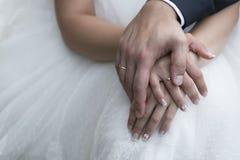 Manos de novia y del novio con los anillos de bodas (foco suave) Cruz p Fotos de archivo