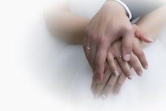 Manos de novia y del novio con los anillos de bodas (foco suave) Cruz p Fotografía de archivo libre de regalías