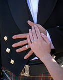 Manos de novia y del novio que se reclinan sobre el estómago del novio Foto de archivo libre de regalías
