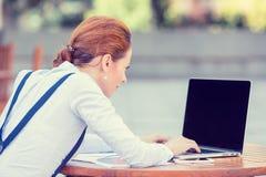 Manos de reclinación del empresario de la mujer de negocios en el teclado que mira en la pantalla del ordenador portátil del orde foto de archivo