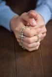 Manos de rogación del hombre con un rosario Imágenes de archivo libres de regalías