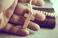 Manos de rogación del pobre hombre con un rosario encendido en praye de la tabla del cemento Fotografía de archivo libre de regalías