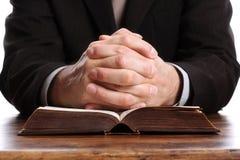Manos de rogación en una biblia abierta Fotografía de archivo