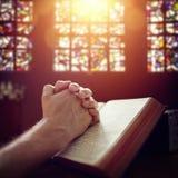 Manos de rogación en una biblia santa imagen de archivo libre de regalías