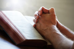 Manos de rogación en una Sagrada Biblia Fotografía de archivo libre de regalías