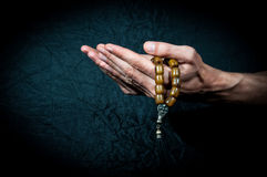 Manos de rogación que sostienen el rosario imagenes de archivo