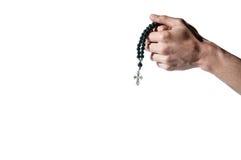 Manos de rogación que sostienen un rosario con la cruz Fotos de archivo libres de regalías