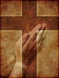 Manos de rogación y cruz cristiana Imagen de archivo libre de regalías