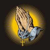 Manos de rogación con el rosario y shihning Fotografía de archivo