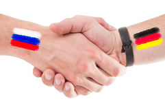 Manos de Rusia y de Alemania que sacuden con las banderas Fotos de archivo