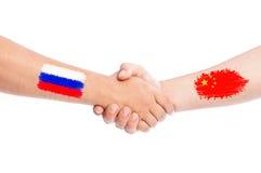 Manos de Rusia y de China que sacuden con las banderas Imagen de archivo libre de regalías