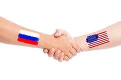 Manos de Rusia y de los E.E.U.U. que sacuden con las banderas Fotos de archivo