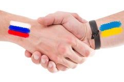 Manos de Rusia y de Ucrania que sacuden con las banderas Fotos de archivo