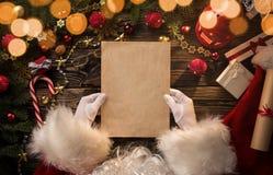 Manos de Santa Claus que llevan a cabo la letra en blanco Foto de archivo libre de regalías