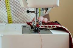 Manos de Seamstres que cosen con el paño rojo de la máquina de coser imagenes de archivo