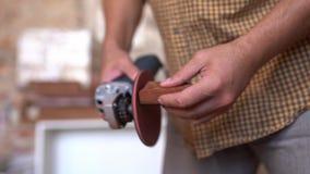 Manos de un carpintero que sostiene una amoladora para pulir la madera almacen de metraje de vídeo
