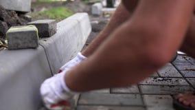 Manos de un constructor en sus manos con guantes anaranjadas con una colocación del martillo que pone las nuevas piedras de pavim almacen de metraje de vídeo