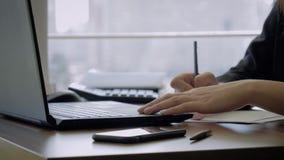Manos de un encargado superior Sitting At Workplace y trabajo de la mujer en un ordenador portátil metrajes
