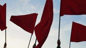 Manos de un grupo de personas que agita banderas rojas contra el cielo azul almacen de video