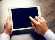 Manos de un hombre que lleva a cabo el dispositivo en blanco de la tableta sobre la tabla del espacio de trabajo Foto de archivo