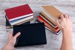 Manos de un hombre que sostiene una tableta y una pila de libros El concepto de conocimiento fotografía de archivo libre de regalías