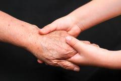 Manos de un joven y de mujeres mayores Foto de archivo