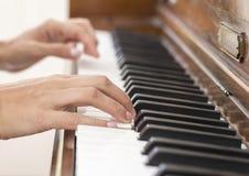 Manos de un músico que juega un piano de madera del vintage Fotografía de archivo libre de regalías