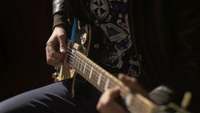Manos de un músico que toca la guitarra eléctrica almacen de metraje de vídeo