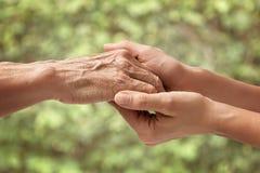Manos de un mayor mayor que lleva a cabo la mano de una mujer imagen de archivo libre de regalías