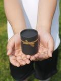 Manos de un muchacho que lleva a cabo un presente Foto de archivo