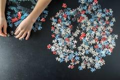 Manos de un niño que hace un rompecabezas Imagenes de archivo