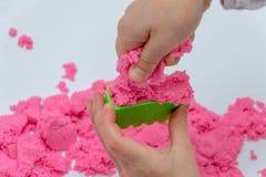Manos de un niño que juega con la arena mágica rosada fotografía de archivo