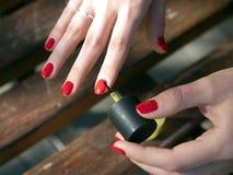 Manos de una chica joven que hace una manicura al aire libre fotos de archivo
