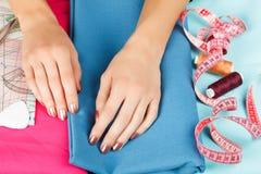 Manos de una costurera en el trabajo Foto de archivo libre de regalías