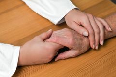 Manos de una enfermera y de un mayor anterior Foto de archivo libre de regalías