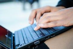 Manos de una escritura de la mujer con un ordenador portátil Imagenes de archivo