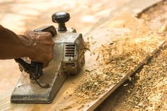 Manos de una madera de cepillado del carpintero Imagen de archivo