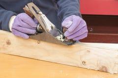 Manos de una madera prevista carpintero Imagen de archivo libre de regalías