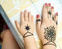 Manos de una madre y de un niño con los tattoes negros indios tradicionales de una flor fotos de archivo libres de regalías