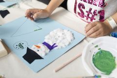 Manos de una muchacha de 10 años que hace un arte de la Navidad Imagen de archivo libre de regalías
