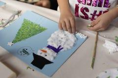 Manos de una muchacha de 10 años que hace un arte de la Navidad Foto de archivo