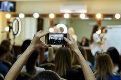 Manos de una muchacha con un teléfono en el fondo borroso de una clase principal Imagenes de archivo